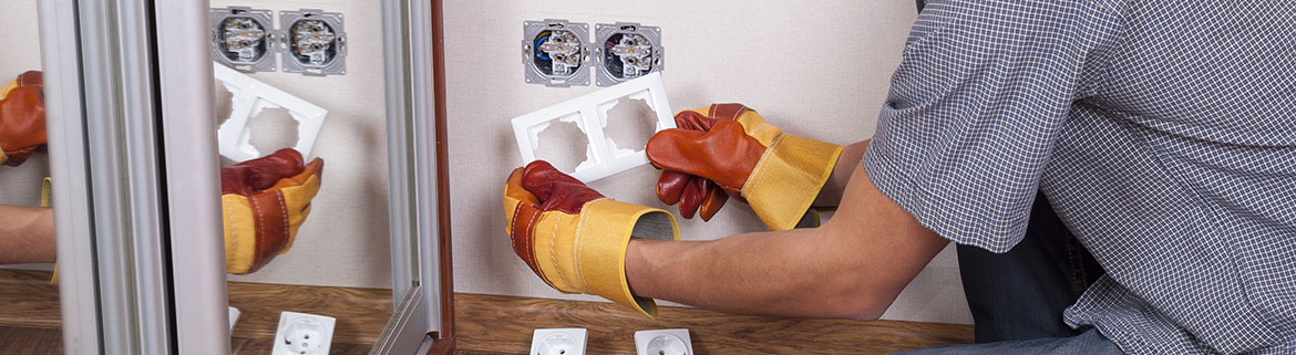 Electrician installs paired socket on the wall